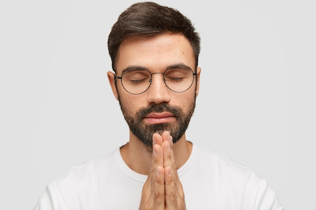焦点を当てたひげを生やした若い男のモデルは、手のひらを祈りのジェスチャーに保ち、幸運を信じています。 無料写真