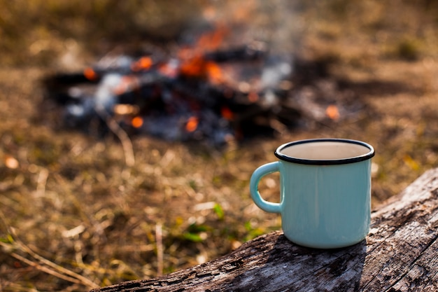 Focused blue cup of coffee and burned out campfire Free Photo