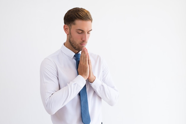 Focused business man praying and keeping hands together. Free Photo