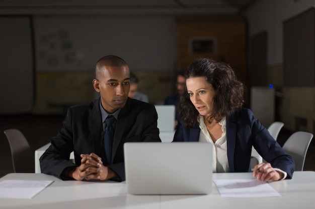 Focused business partners looking at laptop in office Free Photo