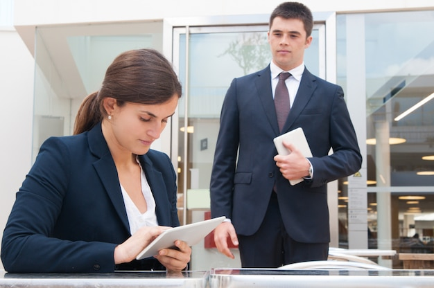 Focused business woman using tablet and coworker standing near Free Photo