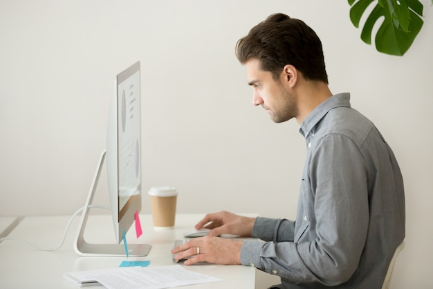 Focused businessman working on computer with project statistics, side view Free Photo