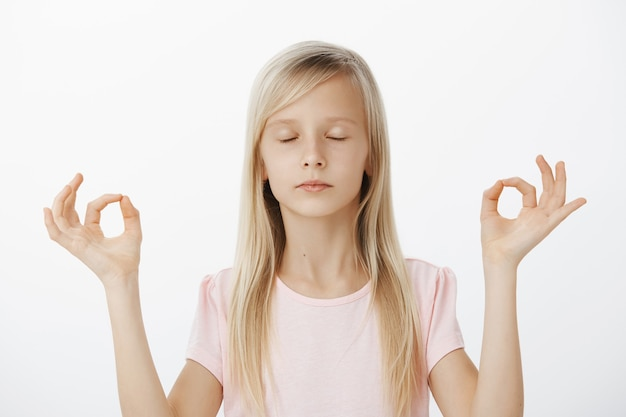 Ragazza europea calma focalizzata che prova la meditazione con la mamma. ritratto di fiducioso di bell'aspetto bambino con capelli biondi, chiudendo gli occhi e in piedi sopra il muro grigio in posa yoga con gesti zen Foto Gratuite
