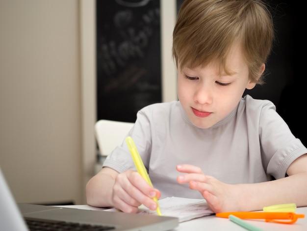 Сосредоточенный ребенок пишет в своей тетради среднего снимка Бесплатные Фотографии