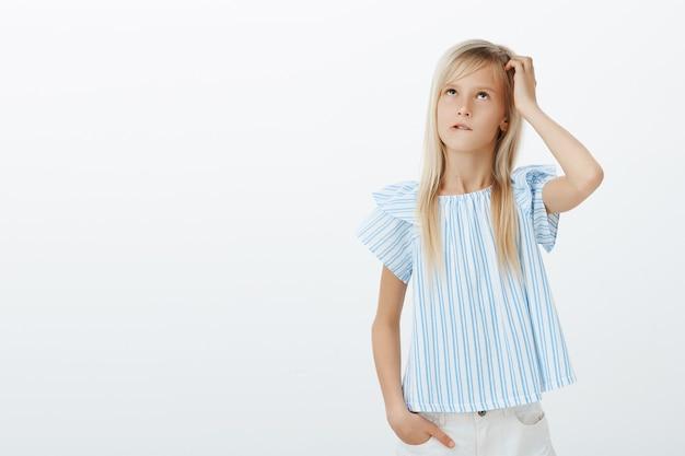 Ragazza incapace concentrata che prova a calcolare in mente vicino alla lavagna. ritratto di bambino interrogato confuso in elegante camicetta blu, grattandosi la testa e guardando in alto, mordendosi il labbro mentre pensa al muro grigio Foto Gratuite