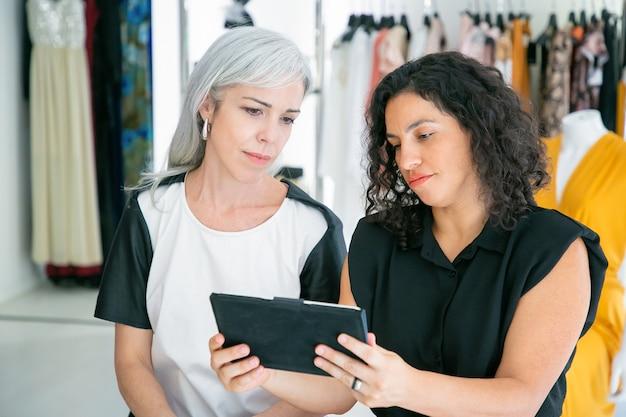 Целенаправленная встреча покупателя и продавца в магазине модной одежды, сидение вместе и использование планшета, обсуждение одежды и покупок. потребительство или концепция покупок Бесплатные Фотографии