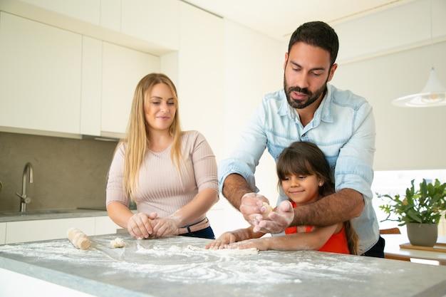 焦点を当てたお父さんが乱雑に小麦粉を使って台所のテーブルに生地を作るように娘に教える。若い親と彼らの女の子が一緒にパンやパイを焼きます。家族の料理のコンセプト 無料写真