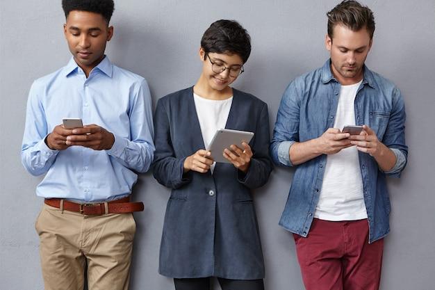 さまざまな国のファッショナブルな若者に焦点を当て、タブレットやスマートフォンで注意深く情報を読む 無料写真