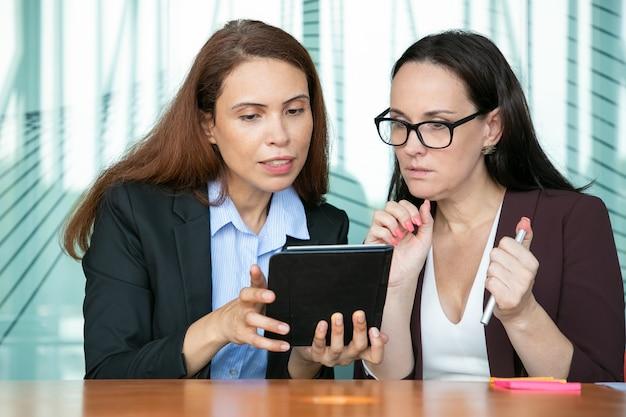 タブレットでコンテンツを一緒に見て、会議室のテーブルに座っているときに興奮して画面を見ている女性の同僚に焦点を当てました。 無料写真