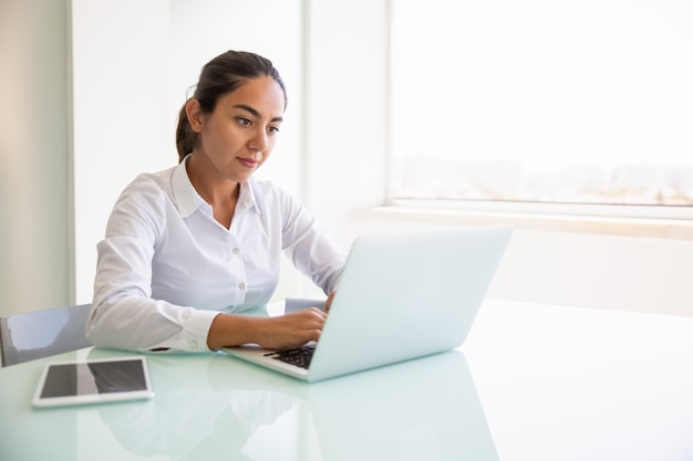 Focused female professional working on computer Free Photo