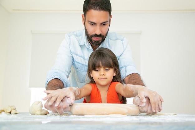 焦点を当てた女の子と彼女のお父さんは、小麦粉が乱雑にキッチンテーブルで生地を練り、転がします。 無料写真