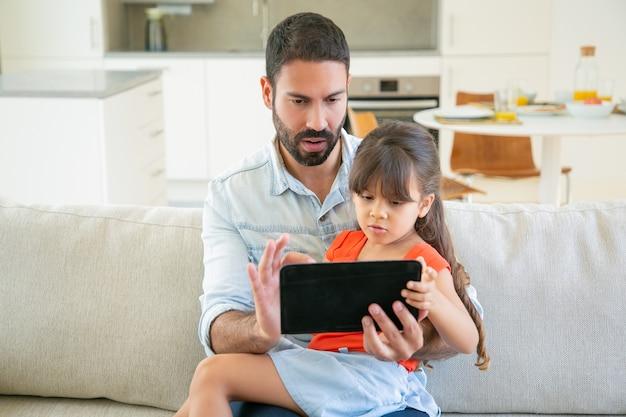 焦点を当てた女の子と彼女のお父さんは、オンラインアプリを使用して、映画を見たり、タブレット画面で一緒に読んだりしています。 無料写真