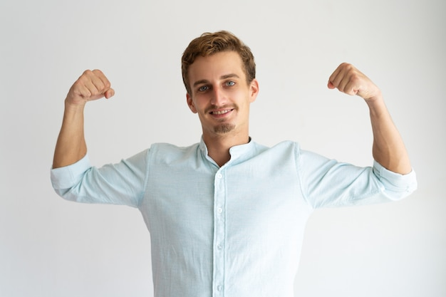 Focused guy in white casual shirt showing strength gesture. Free Photo