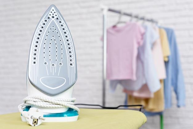 Focused iron on yellow ironing board Free Photo