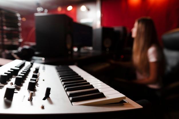 Focused keyboard and blurred woman in studio Free Photo