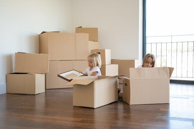 Bambini piccoli concentrati che disimballano le cose nel nuovo appartamento, si siedono sul pavimento e prendono oggetti da scatole di cartone aperte Foto Gratuite