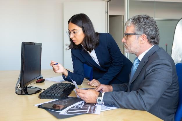 남성 비즈니스 리더와 여성 비서가 Pc 모니터에 통계 보고서를보고 종이 거래 차트를 들고 집중했습니다. 측면보기. 금융 전문가 개념 무료 사진