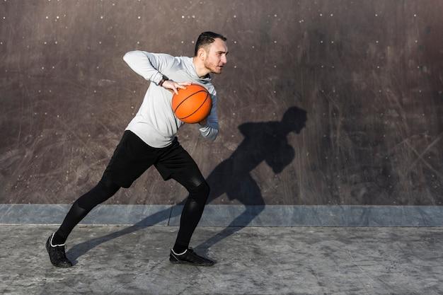 Focused man playing basket outside Free Photo