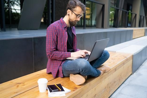 ノートパソコンと木製のベンチにあぐらをかいて座って焦点を当てた男 無料写真
