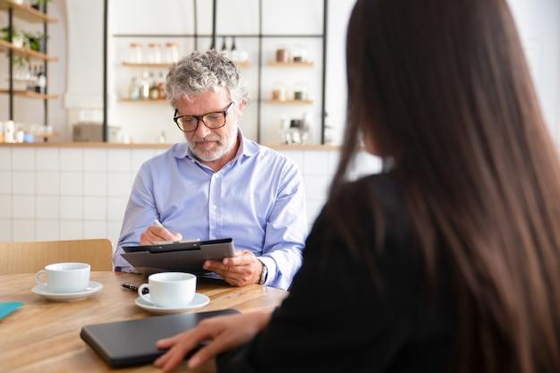 Incontro d'affari maturo focalizzato con l'agente davanti a una tazza di caffè al lavoro femminile e firma dell'accordo Foto Gratuite