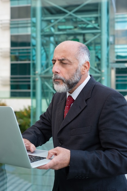 Focused mature businessman with laptop checking email Free Photo