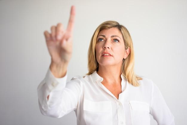 99d8311d4e34 Focused mature caucasian woman pointing index finger up. Premium Photo