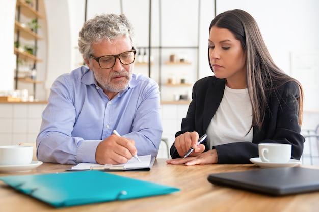 Целенаправленный зрелый клиент читает соглашение и консультант по деталям, указывая ручкой на бумагу Бесплатные Фотографии