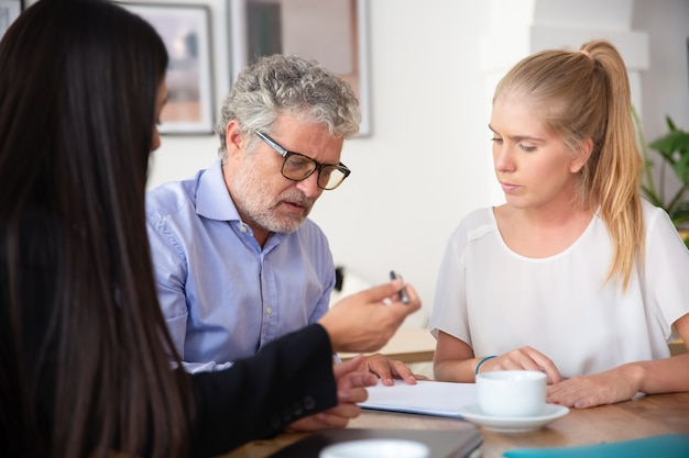 Focused mature man reading document, his female colleague giving pen to him for signing Free Photo
