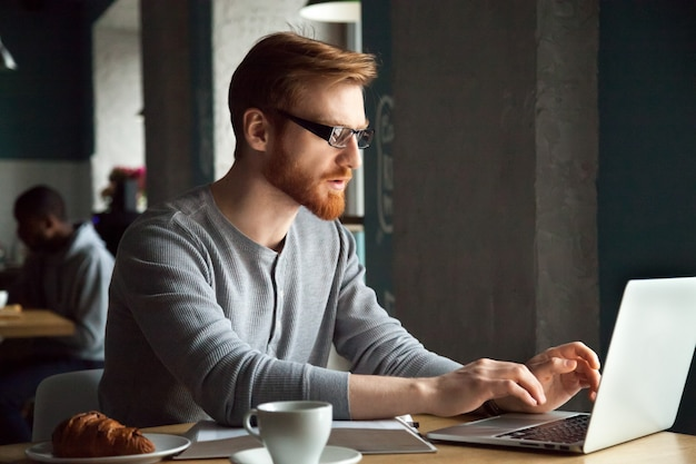 Focused millennial redhead man using laptop sitting at cafe table Free Photo