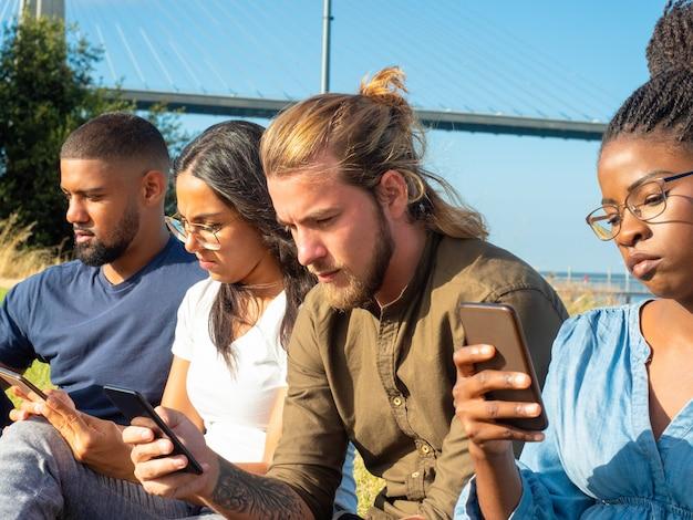 Focused multiracial friends using smartphones Free Photo