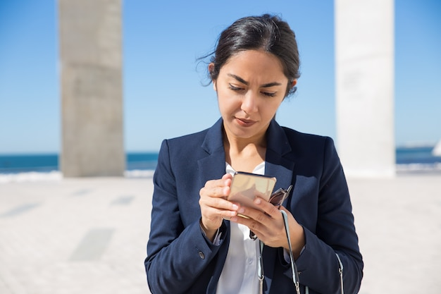 Focused office assistant reading on phone screen Free Photo