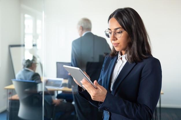 O atributo alt desta imagem está vazio. O nome do arquivo é focused-office-lady-glasses-using-tablet-while-two-mature-businessmen-discussing-work-glass-wall-copy-space-communication-concept_74855-14243.jpg