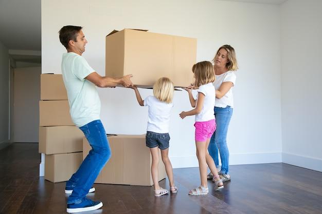 Сосредоточенные родители и две девочки вместе несут коробки в новую пустую квартиру Бесплатные Фотографии