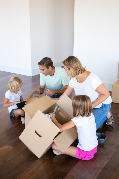 Genitori e bambini concentrati che disimballano le cose nel nuovo appartamento, si siedono sul pavimento e prendono oggetti da scatole aperte Foto Gratuite