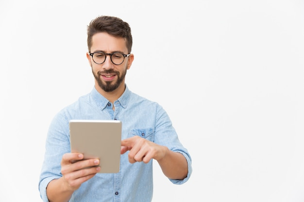 Focused positive guy watching content on tablet Free Photo