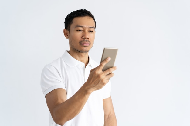 Focused serious guy texting message Free Photo