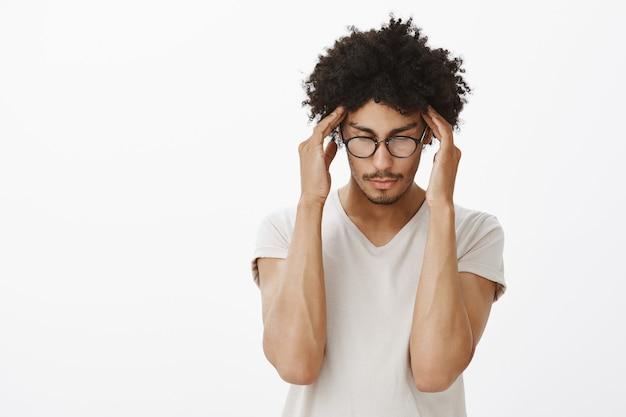 Uomo dalla pelle scura dall'aspetto serio concentrato, studenti di brainstorming, sfregamento delle tempie come concentrati Foto Gratuite