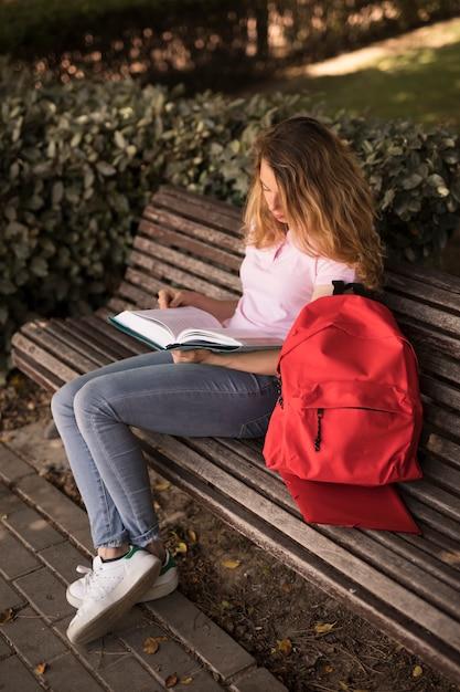 集中している10代女性のベンチで本を読んで 無料写真