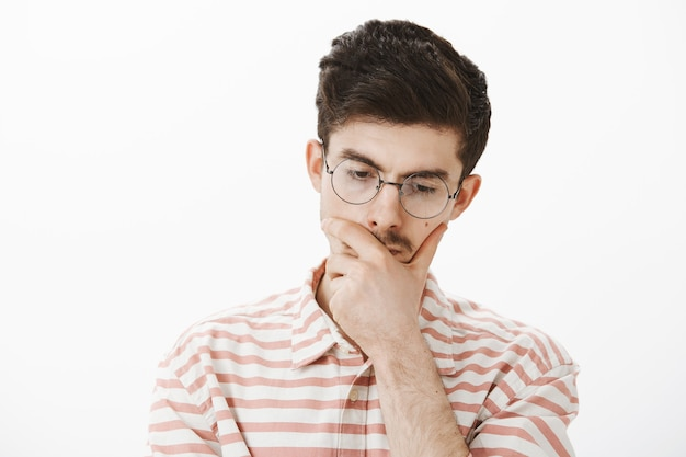 Focused thinking male program developer in trendy glasses, tilting head down and touching chin, being concerned while making decision or planning something over gray wall Free Photo