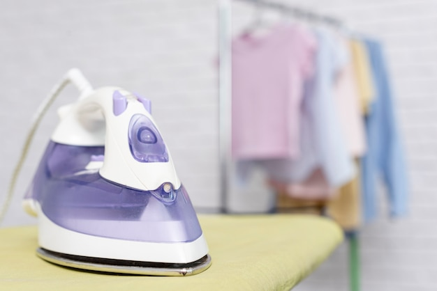 Focused violet iron placed on ironing board Free Photo