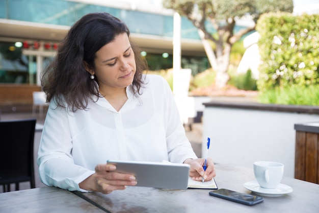 Focused woman making notes, working and using tablet in cafe Free Photo