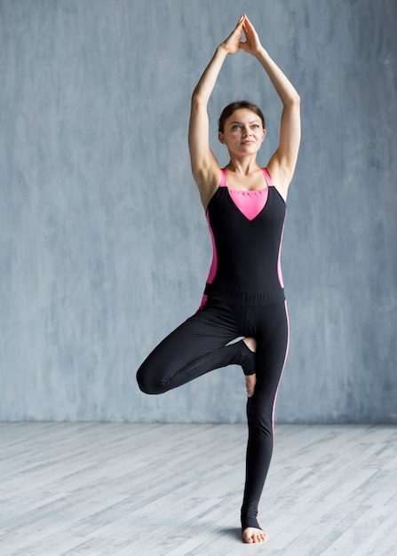 Focused woman practicing yoga in a tree pose Free Photo