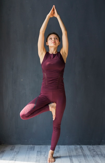 Focused woman standing in a tree pose with arms extended above her Free Photo