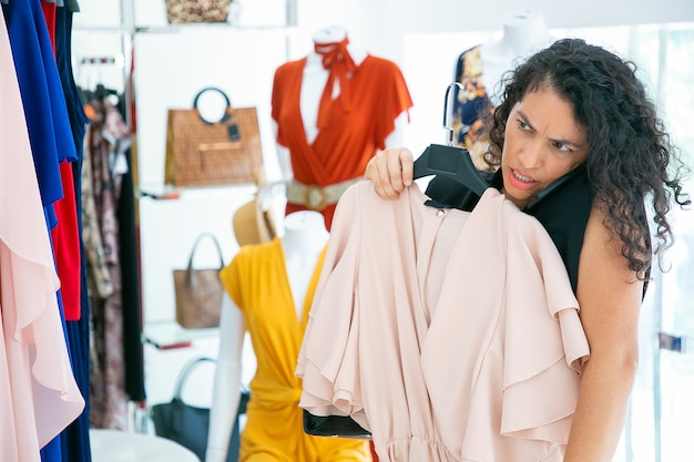 Focalizzato donna parlando al cellulare durante lo shopping nel negozio di moda, applicando il vestito a se stessa e guardandosi allo specchio. colpo medio. cliente boutique o concetto di vendita al dettaglio Foto Gratuite