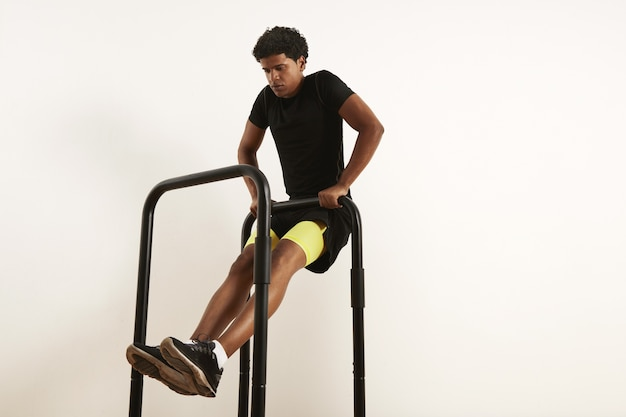 Сосредоточенный молодой афро-американский спортсмен в черной спортивной одежде выполняет тяги собственного веса на мобильных барах, изолированных на белом Бесплатные Фотографии