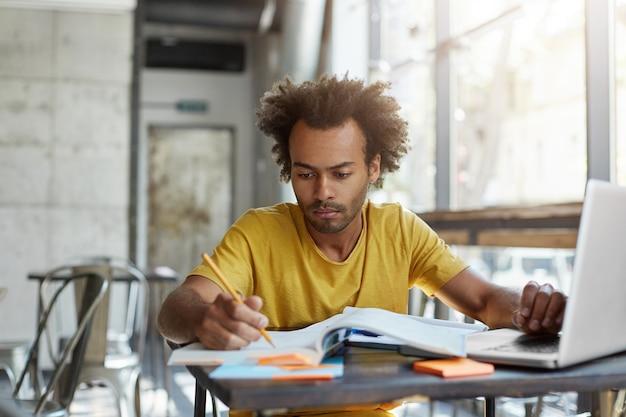 オープンラップトップコンピューターの前のカフェのテーブルに座って、生徒のコピーブックをチェックする若いアフロアメリカン英語教師に焦点を当てた。大学の食堂で深刻な黒人男性学生学習レッスン 無料写真