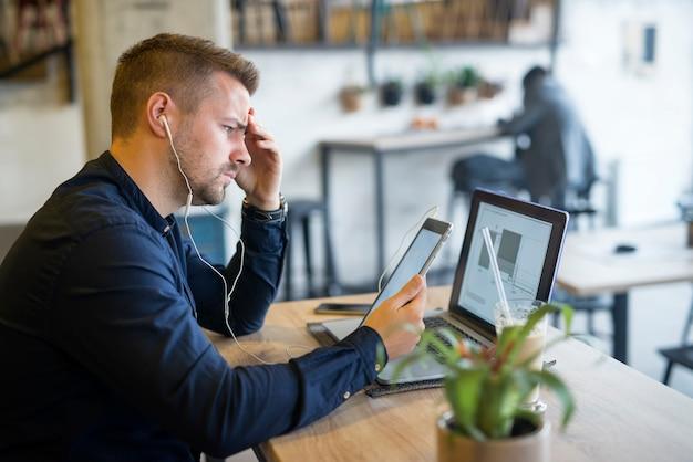 Focalizzato giovane barbuto libero professionista pensando al suo progetto sul computer nel ristorante bar caffetteria Foto Gratuite