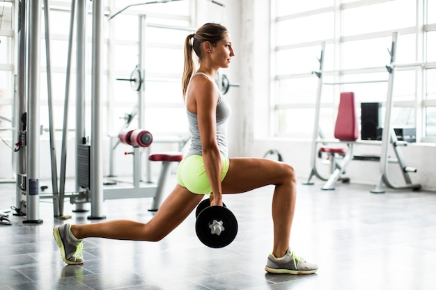 Focused young beautiful woman lifting weights in a gym Premium Photo