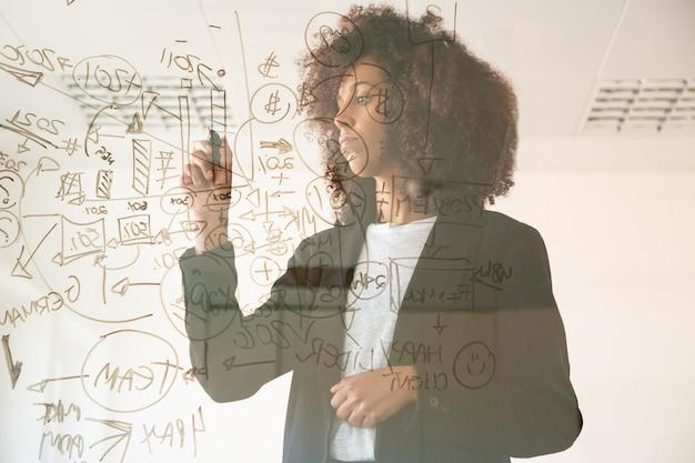 Focalizzato giovani imprenditrici scrivendo a bordo virtuale. giovane responsabile femminile afroamericano concentrato che tiene indicatore e che fa annotato sul grafico. strategia, business e concetto di gestione Foto Gratuite