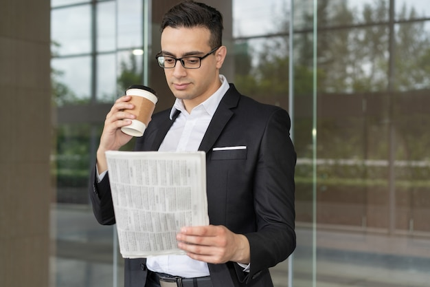Free Photo | Focused young investor looking through latest financial news